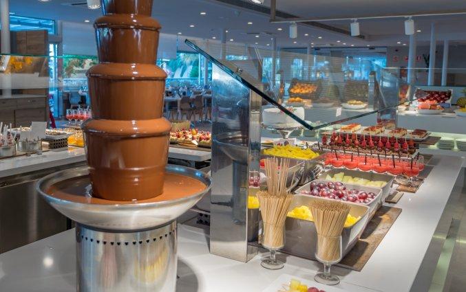 Chocoladefontein van buffet in Buffetzaal met stoelen van Taurus Aquapark resort aan de Costa Brava