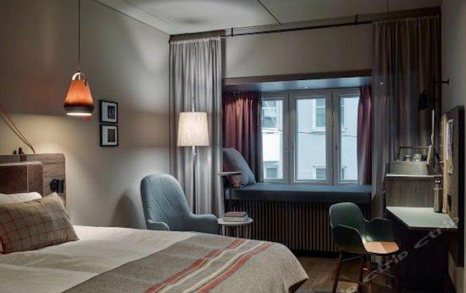 Slaapkamer met bed en loungehoek in raam van hotel downtown Camper