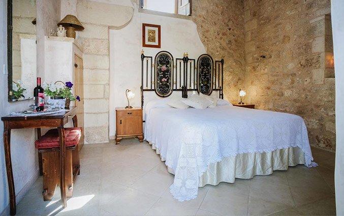 Tweepersoonsbed in kamer met muur Hotel Borgoterra in Puglia
