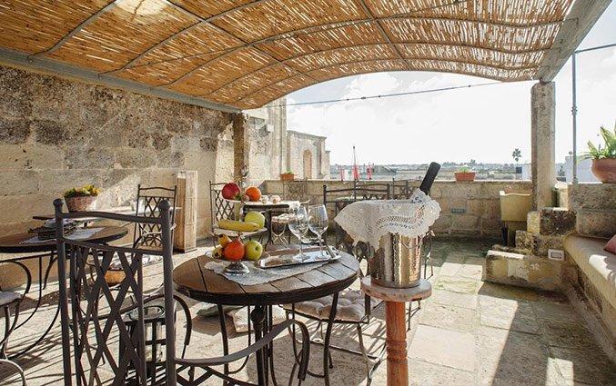 Overdekt buitenterras met stoelen en tafels van Hotel Borgoterra in Puglia