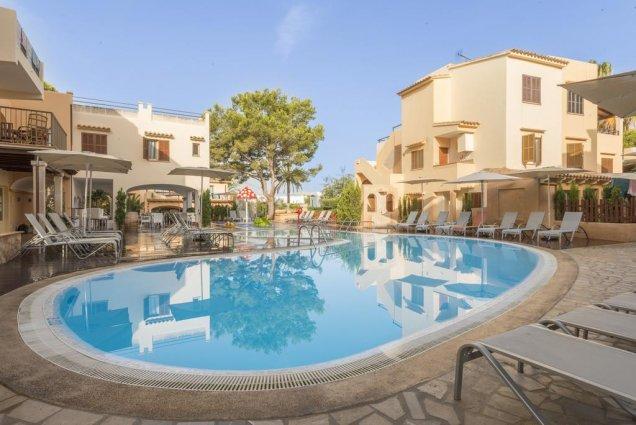 Zwembad met op de achtergrond een appartement van Playa Ferrera zonvakantie Mallorca