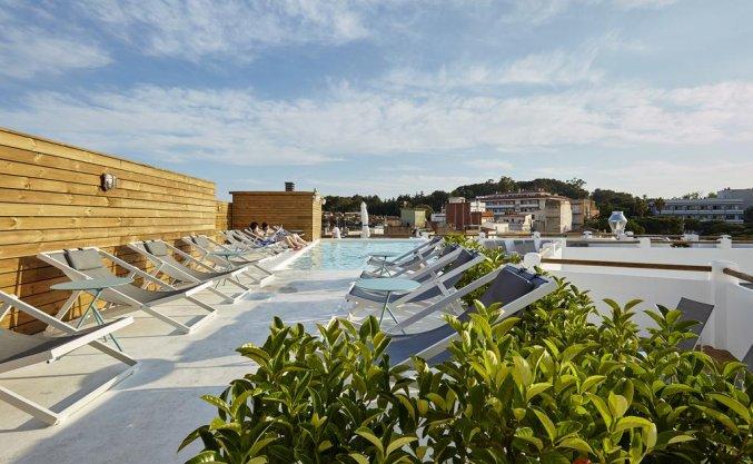 Ligbedden en zwembad van Hotel Delamar in Lloret de Mar