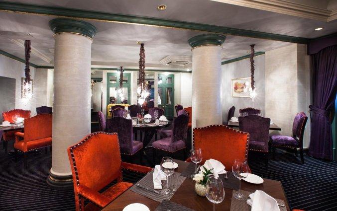 Restaurant met paarse en rode stoelen van hotel Grand Palace stedentrip Riga
