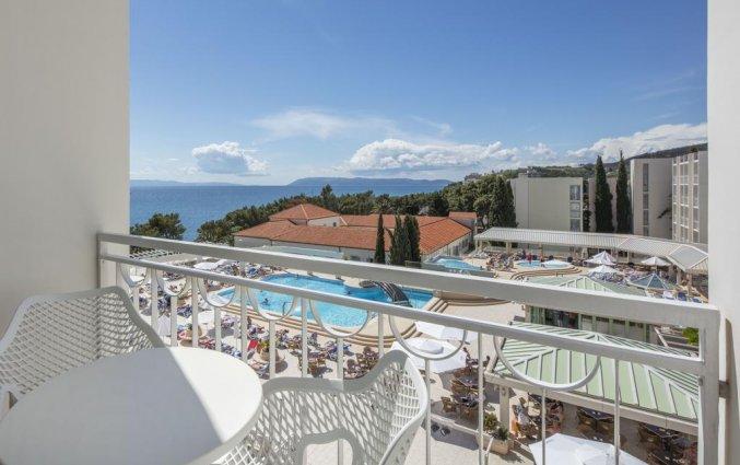 Balkon met uitzicht op het zwembad en de zee van Hotel Bluesun Alga in Dalmatië